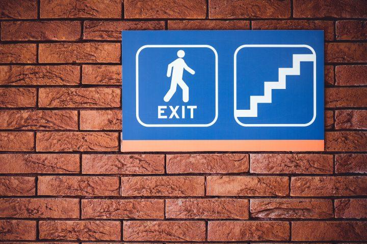 Kuvassa on exit-merkki ja juokseva hahmo sekä portaiden merkki