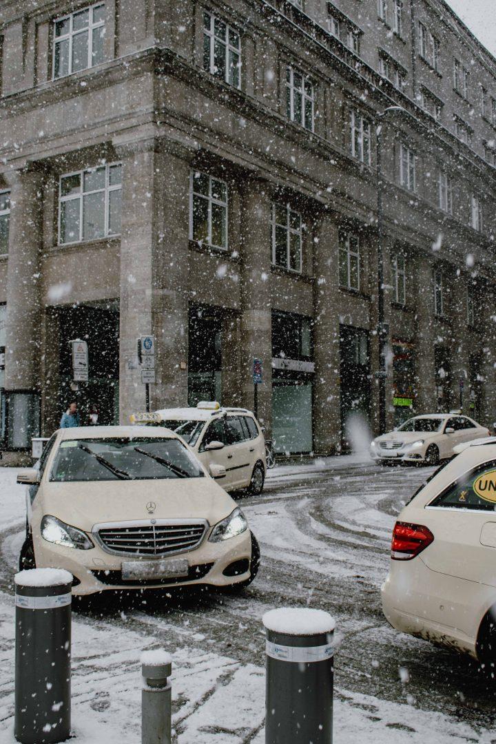 kuvassa on useita takseja jonossa lumisateessa