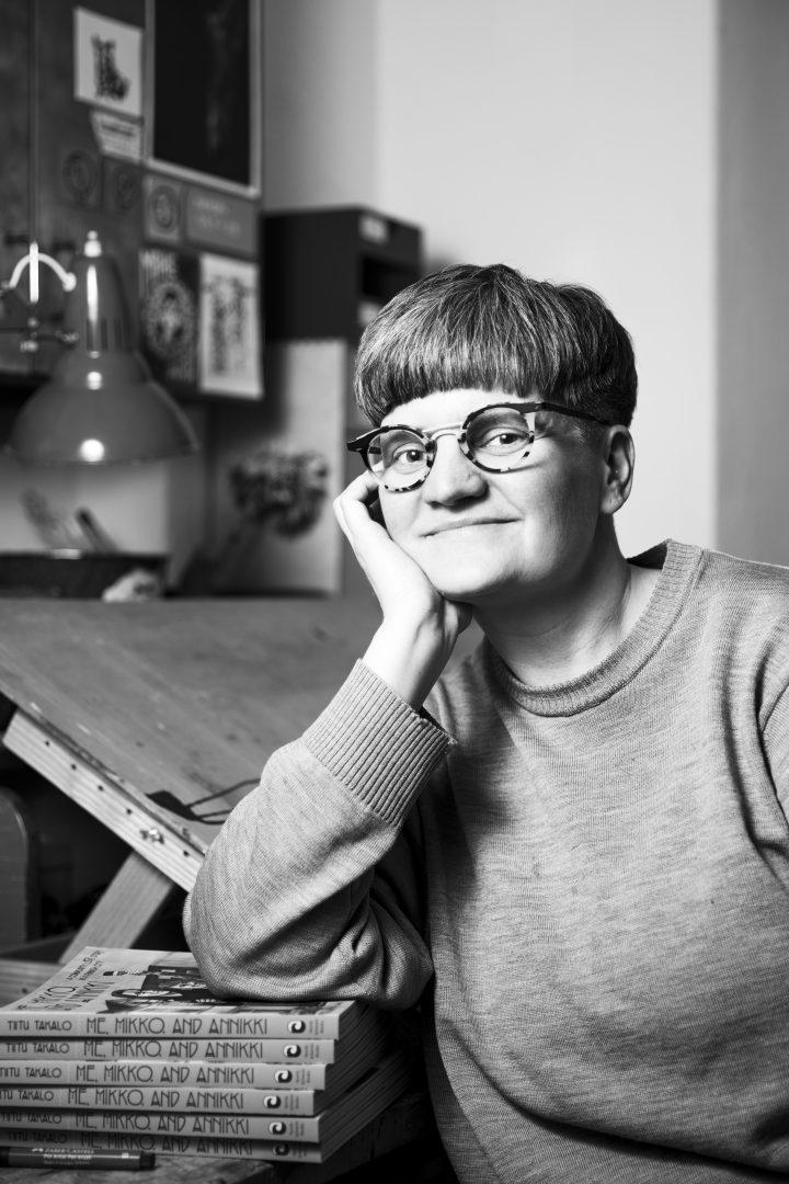 Kuvassa on lyhyttukkainen silmälasipäinen nainen piirustuspöydän ääressä
