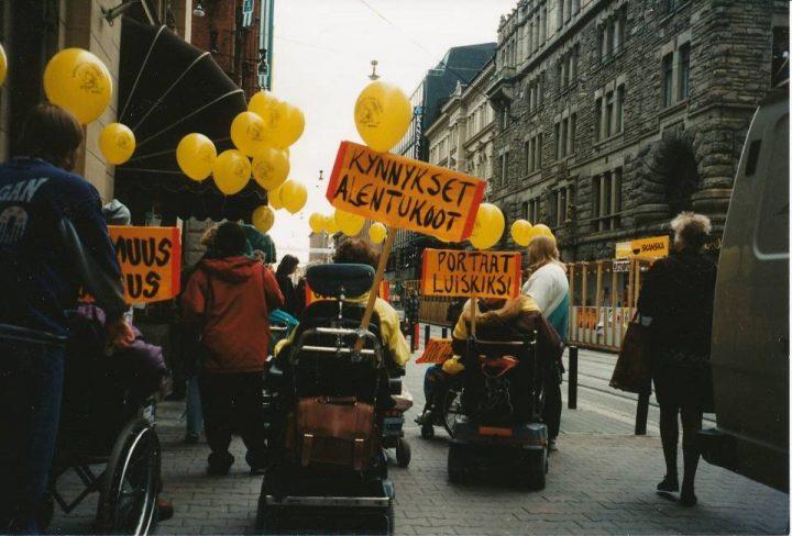 Kuva mielenosoituksesta, jossa on ihmisiä apuvälineineen.