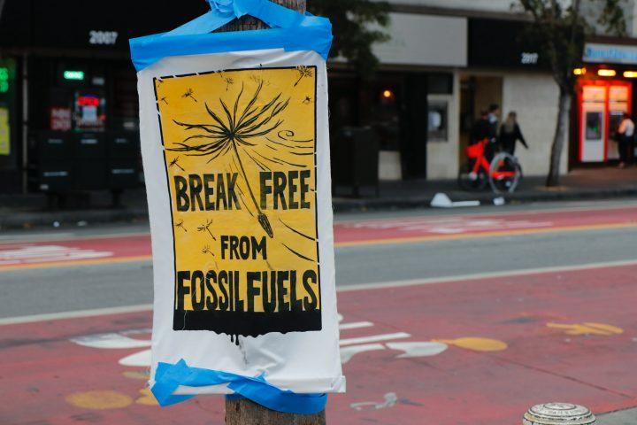 Kuvassa on tolppaan kiinnitetty lappu jossa lukee: Break free from fossilfuels.